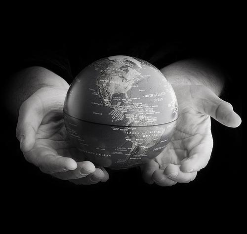 Foto av verden holdt inni to hender